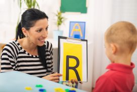 Speech therapist teaches a child to say the letter R